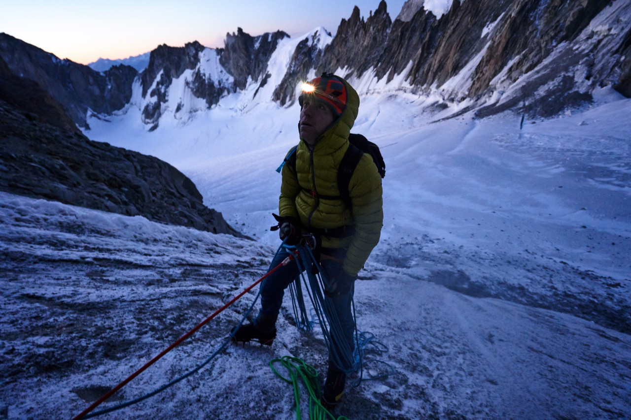 Willis Morris layering a Fenrir down jacket on a cold belay