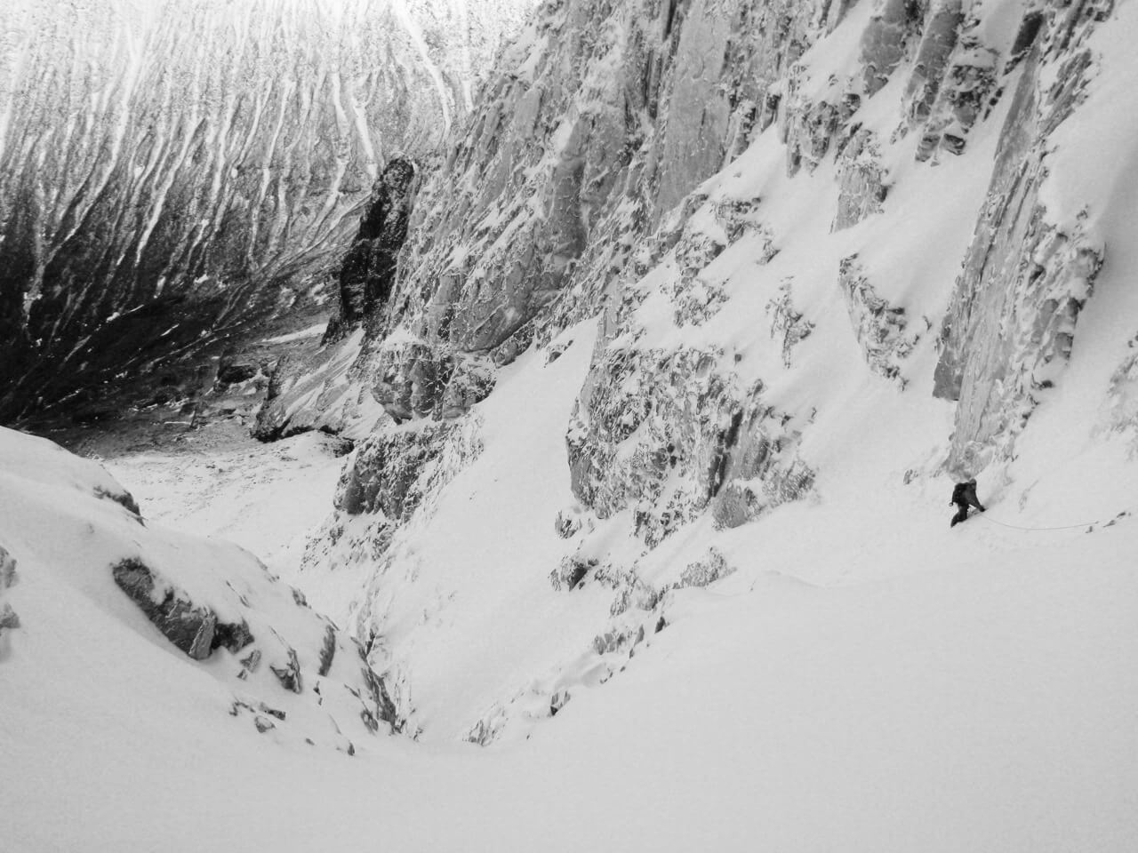 A climber in a snow gully in the middle of the route