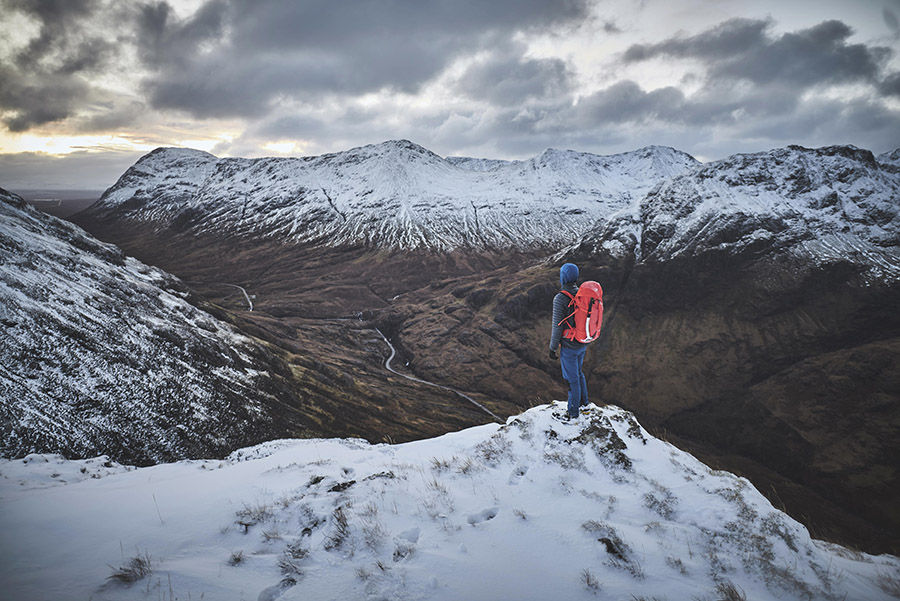 A walker standing on top of a hill overlooking Glen Coe
