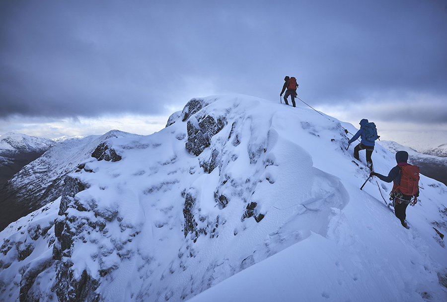 A team of three climbers on a snowy ridge on Aonach Eagach