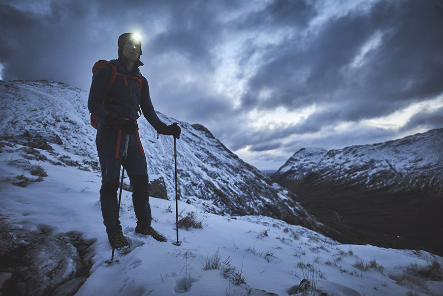 A walker wearing a headlamp and carrying trekking poles standing on Am Bodach in the early morning