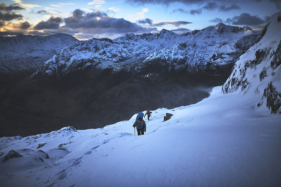 Two walkers on a snow slope on Am Bodach at dawn