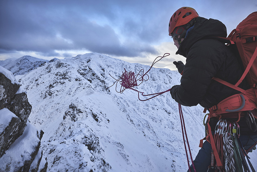 A climber throws a rope off Meall Dearg to abseil from
