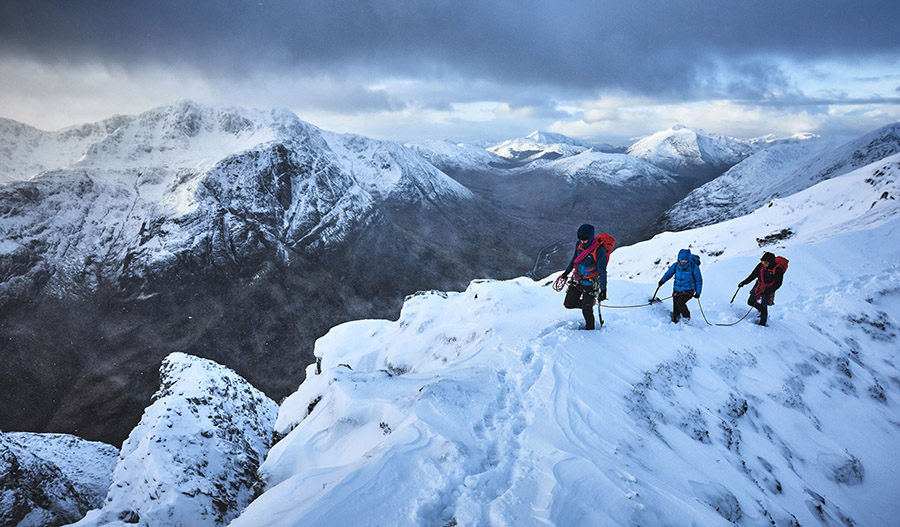 A team of three climbers on a snow slope on Aonach Eagach